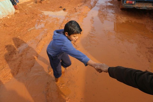 Person helping a child getting out of the mud