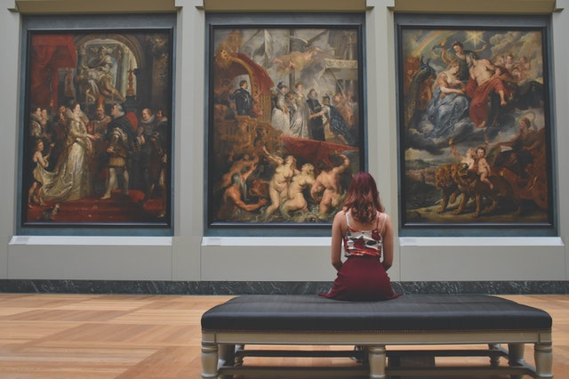 Woman admiring paintings at a museum